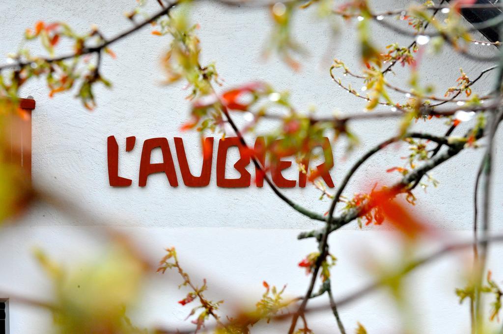 Photographie du nom du restaurant de l'Aubier vu à travers des branches d'arbres