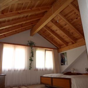 Une chambre sous les pans du toit en bois